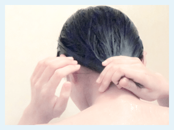 髪の毛をしぼる女性